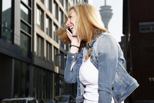 Germany, Duesseldorf, laughing blond woman telephoning with smartphone - RHF000839