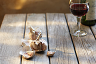 Garlic cloves and glass of red wine on wood - KSWF001487