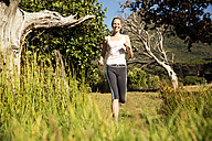 Smiling woman jogging in rural landscape - TOYF000331