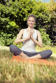 Smiling woman practising yoga in a meadow - TOYF000340