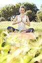 Woman practising yoga in a meadow - TOYF000343