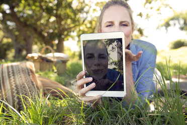 Woman with digital tablet lying on meadow showing a selfie - TOYF000361