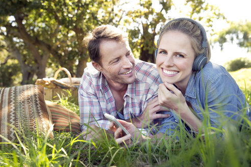 Happy couple lying on meadow with woman listening to music from smartphone - TOYF000373