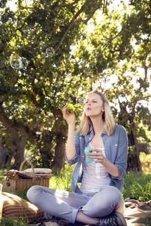 Woman on meadow blowing soap bubbles - TOYF000388