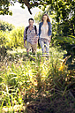 Smiling couple hiking hand in hand in rural landscape - TOYF000394