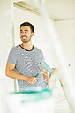 Smiling young man renovating holding paint roller - UUF004162