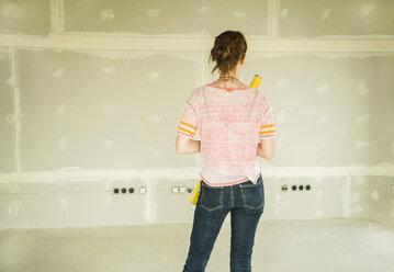 Young woman renovating standing at blank wall - UUF004169