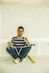 Smiling young man sitting at blank wall holding pocket rule - UUF004184