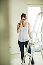 Young woman renovating talking on cell phone - UUF004205
