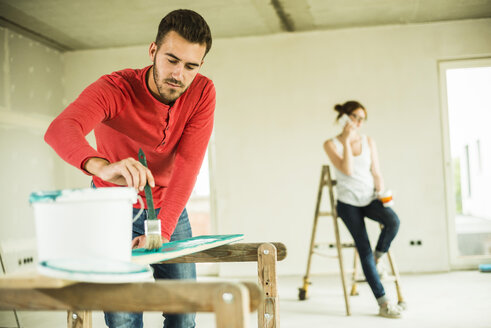 Young man painting wooden board with woman in background on the phone - UUF004209