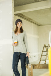 Smiling young woman having a coffee break from renovating - UUF004224
