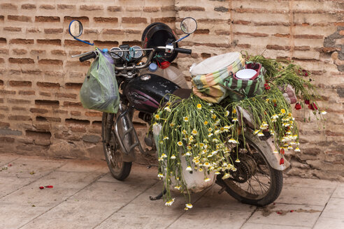 Morocco, Marrakesh, parked moped loaded with bags and flowers - HSK000034