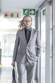 Portrait of businessman with dreadlocks wearing suit - ZEF006163