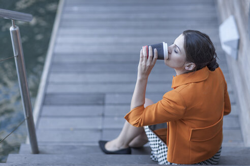 Woman sitting on steps drinking coffee - ZEF005874