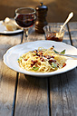 Dish of spaghetti with tomato pesto and grated parmesan and glass of red wine - KSWF001477