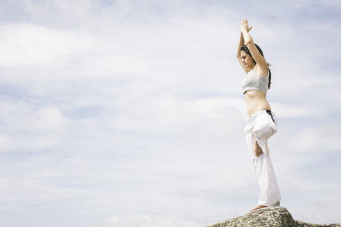 Woman doing yoga exercises on a mountain - ABZF000037