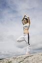 Woman doing yoga exercises on a mountain - ABZF000039