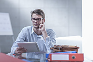 Portrait of young businessman using digital tablet at his desk - ZEF005047