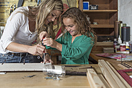 Mother and daughter doing crafts in home garage - ZEF004856