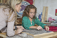 Mother and daughter doing crafts in home garage - ZEF004867