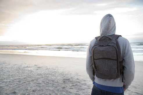 Young man with backpack on beach at sunrise - TOYF000411