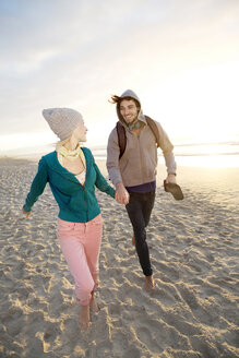 Young couple walking on beach at sunrise - TOYF000414