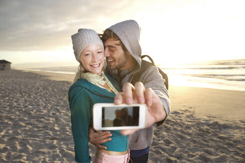 Young couple taking a selfie on beach at sunrise - TOYF000417
