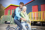 Young couple riding bicycle at colorful beach huts - TOYF000454
