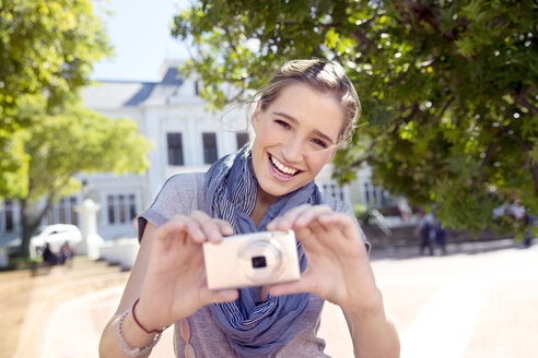 Portrait of happy young woman with camera - TOYF000526
