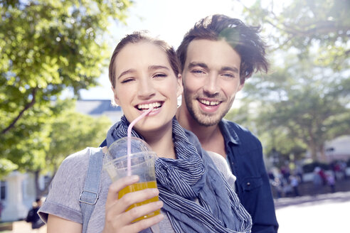 Smiling young couple outdoors with soft drink - TOYF000540