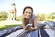 Young woman lying on blanket in park listening to music - TOYF000546