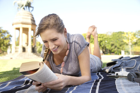 Young woman lying on blanket in park reading a book - TOYF000549