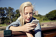 Young woman on park bench looking on cell phone - TOYF000558