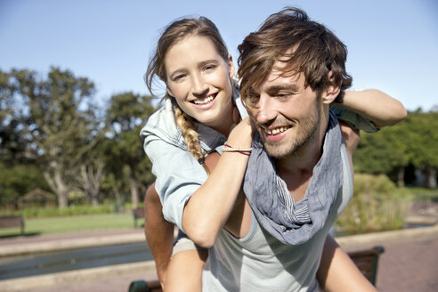 Happy young man carrying girlfriend piggyback - TOYF000570
