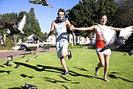 Enthusiastic young couple chasing pigeons in park - TOYF000573