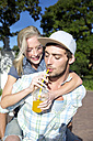 Young man drinking soft drink carrying girlfriend piggyback - TOYF000579