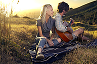 Young couple with guitar on blanket in meadow - TOYF000601