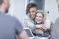 Creative business colleagues having a meeting in office, laughing and hugging - ZEF005728
