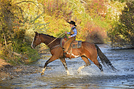 USA, Wyoming, young cowboy riding his horse across river - RUEF001593