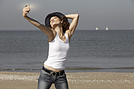 Netherlands, Scheveningen, young woman taking a selfie on the beach - GDF000724