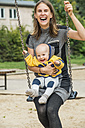 Mother sitting with his little son a swing - FBF000395