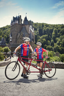 Germany, Rhineland-Palatinate, US American couple standing in front of Eltz Castle with their tandem - MF002082