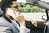 Young black man sitting in convertible, talking on the phone - ABZF000046