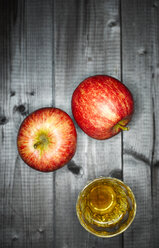 Glass of apple juice and two apples on wood - KSWF001530