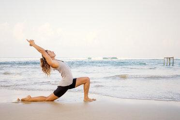 Sri Lanka, Kabalana, young woman practicing yoga on the beach - WV000745