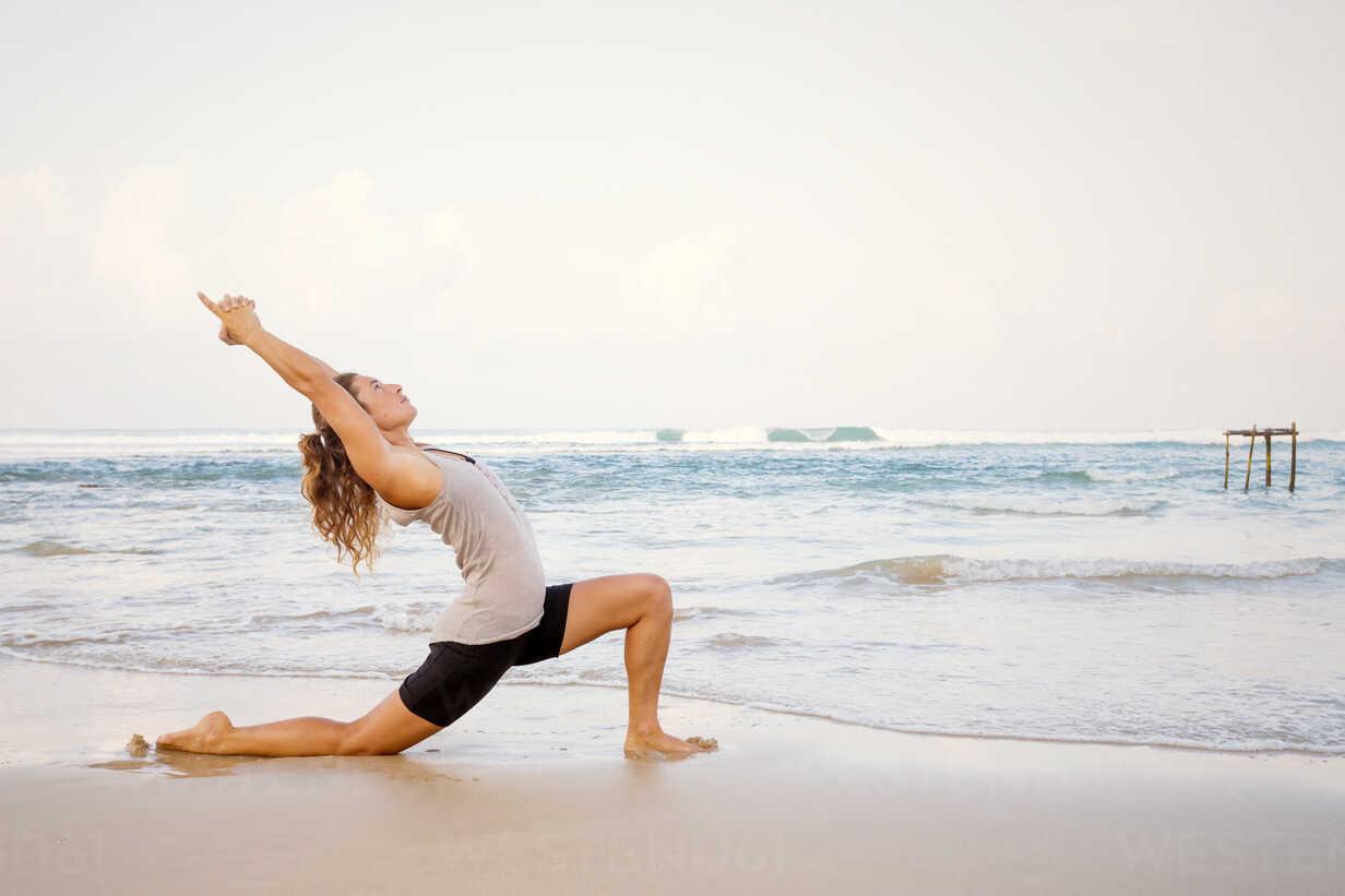 Sri Lanka, Kabalana, young woman practicing yoga on the beach - WV000745 - Valentin Weinhäupl/Westend61