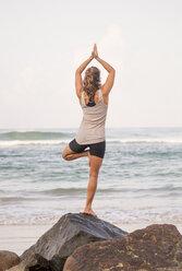Sri Lanka, Kabalana, young woman practicing yoga at the coast - WV000749