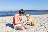 Germany, Kiel, woman sitting with her dog on sandy beach - JFEF000672