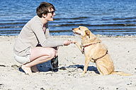 Germany, Kiel, woman with her dog on sandy beach - JFEF000674