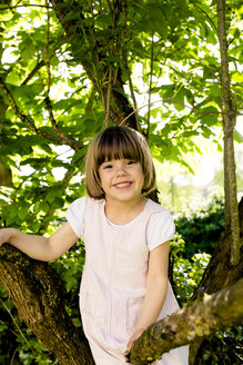 Portrait of smiling little girl climbing in a tree - LVF003394